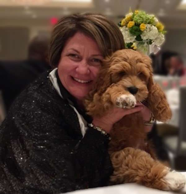 Bio page - Dr Angela Arnold MD with brown dog at event sandy springs atlanta ga